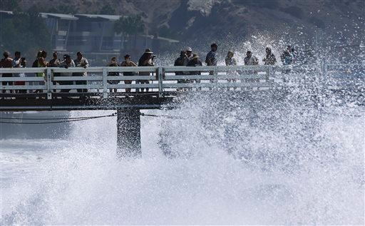 Surf watchers are splashed at the pier in Malibu, Calif., Wednesday, Aug. 27, 2014. (AP Photo/Damian Dovarganes)
