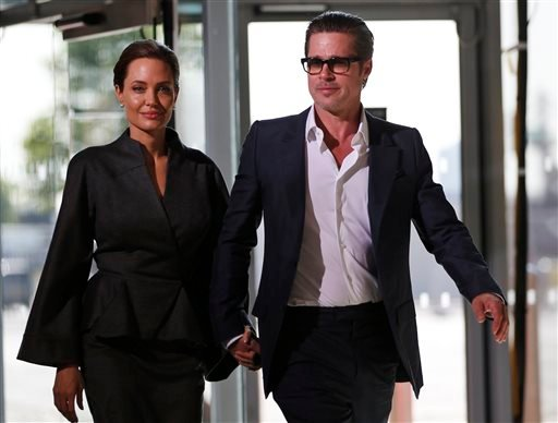 "Friday, June 13, 2014 file photo: U.S. actress Angelina Jolie, Special Envoy of the United Nations High Commissioner for Refugees, accompanied by Brad Pitt arrive at the ""End Sexual Violence in Conflict"" summit in London.(AP Photo/Lefteris Pitarakis,File)"