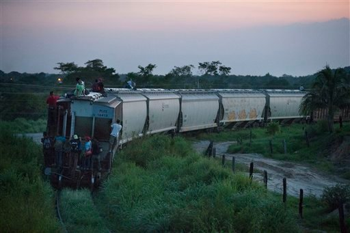 In this Aug. 26, 2014 photo, a handful of Central American migrants cling to a northbound freight train after jumping aboard outside Arriaga, Mexico.