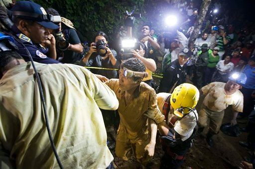 A rescued mines is helped by rescue workers as he leaves on his own feet the entrance to the El Comal gold and silver mine in Bonanza, Nicaragua, Friday, Aug. 29, 2014.