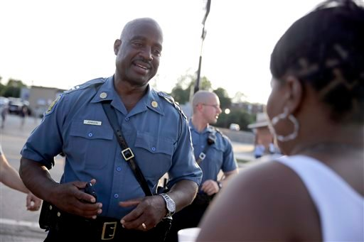 In this Aug. 19, 2014 file photo, Missouri Highway Patrol Capt. Ron Johnson meets with residents while walking the streets of Ferguson, Mo.