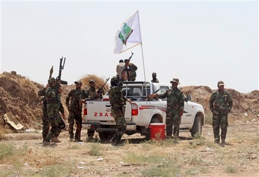 Iraqi security forces and Shiite militiamen chant anti-terrorism slogans after breaking the siege on 15,000 Shiite Turkmens stranded in the farming community town of Amirli, following U.S. airstrikes against Sunni Islamic State group positions, 105 miles