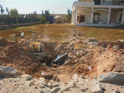 In this photo taken during a tour offered to onlookers and journalists by the Dawn of Libya militia on Sunday, Aug. 31, 2014, damage is seen in the front yard of a building at the U.S. Embassy compound in Tripoli, Libya..