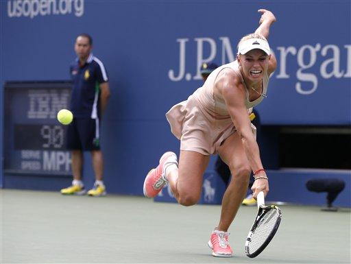 Caroline Wozniacki, of Denmark, returns a shot to Maria Sharapova, of Russia, during the fourth round of the 2014 U.S. Open tennis tournament, Sunday, Aug. 31, 2014, in New York. (AP Photo/Kathy Willens)