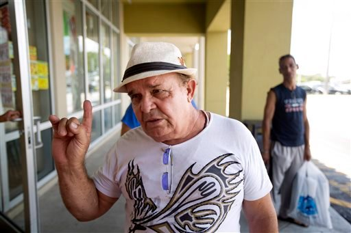 In this Thursday, Aug. 28, 2014 photo, Pedro Rosa, of Havana, discusses a new trade policy, as he stands outside a Miami discount clothing store.