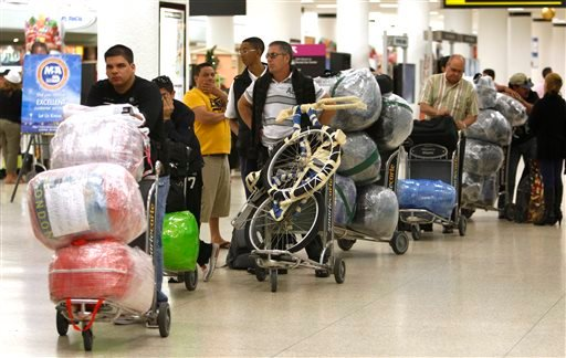 In this Dec. 19, 2011 file photo, travelers wait in line with their luggage at Miami International Airport before traveling Cuba in Miami.