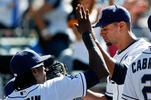 San Diego Padres starting pitcher Tyson Ross is congratulated at the dugout after striking out three consecutive Arizona Diamondbacks batters with a runner on third to end the sixth inning of a baseball game Monday, Sept. 1, 2014, in San Diego.