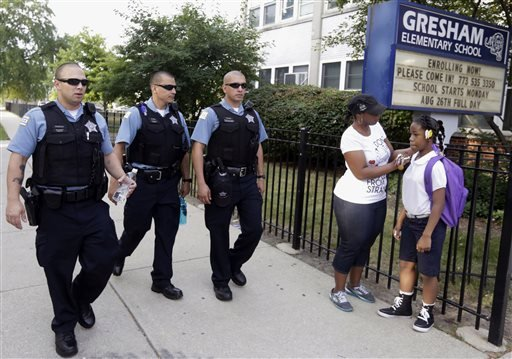 In this Aug. 26. 2013, file photo, Chicago Police patrol the neighborhood at Gresham Elementary School on the first day of classes in Chicago.