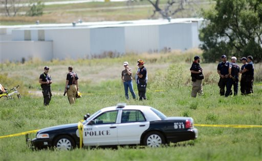 Police and firefighters work on the scene where three people were killed and two others injured after an airplane crashed in a field northwest of the main runway at Erie Municipal Airport while coming in for a landing in Erie, Colo., Sunday, Aug. 31, 2014