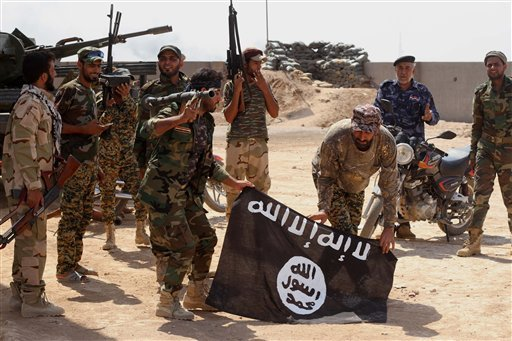 Iraqi security forces hold a flag of the Islamic State group they captured during an operation outside Amirli, some 105 miles (170 kilometers) north of Baghdad, Iraq, Monday, Sept. 1, 2014.