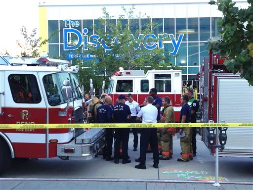 Firefighters confer out side the Nevada Disvory Museum in Reno, Nev., Wednesday Sept. 3, 2014. A minor explosion during a science experiment at the museum burned several children and forced the evacuation of the museum. (AP Photo/Scott Sonner).