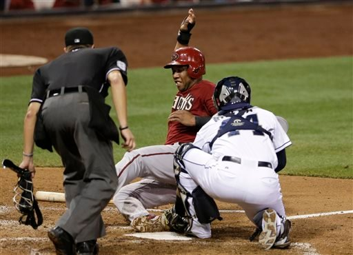 Padres' Rene Rivera, applies the tag too late as Arizona Diamondbacks' Alfredo Marte, behind, scores on a grounder by Josh Collmenter during the fifth inning of a baseball game Wednesday, Sept. 3, 2014, in San Diego. (AP Photo/Gregory Bull)
