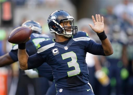 Seattle Seahawks quarterback Russell Wilson winds up to pass against the Green Bay Packers in the first half of an NFL football game, Thursday, Sept. 4, 2014, in Seattle.