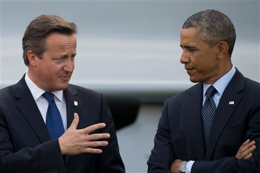 U.S. President Barack Obama, right, speaks with British Prime Minister David Cameron during a flypast at the NATO summit at the Celtic Manor Resort in Newport, Wales on Friday, Sept. 5, 2014. (AP Photo/Jon Super)