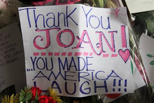 A note and flowers are part of a sidewalk memorial for comedian Joan Rivers at the doorstep of her apartment building, Friday, Sept. 5, 2014 in New York. (AP)