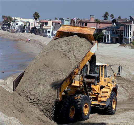 A dump truck works to pile sand on a temporary berm to protect beach front homes on, Friday, Sept. 5, 2014, in Long Beach, Calif.