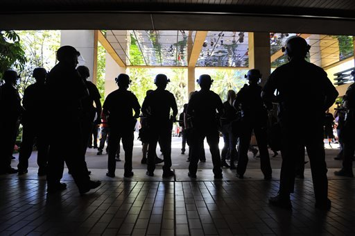 In a July 24, 2012 file photo, police stand at the entrance to city hall in Anaheim, Calif., as demonstrators gather on the steps to protest the death of Manuel Diaz, 25, who died as a result of gunshot wounds sustained during a police pursuit.