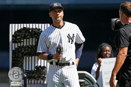 New York Yankees' Derek Jeter holds the microphone as he addresses the crowd during a pregame ceremony honoring the Yankees captain, who is retiring at the end of the season, on Derek Jeter Day at Yankee Stadium in New York, Sunday, Sept. 7, 2014.