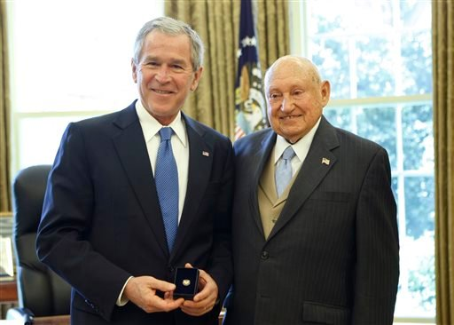 In this April 15, 2008, file photo, then President George W. Bush presents the Lifetime President's Volunteer Service Award to Chick fil-A Inc. founder S. Truett Cathy in the Oval Office of the White House in Washington.