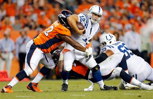 Indianapolis Colts quarterback Andrew Luck (12) is hit by Denver Broncos' Sylvester Williams, left, during the second half of an NFL football game, Sunday, Sept. 7, 2014, in Denver. (AP Photo/Joe Mahoney)