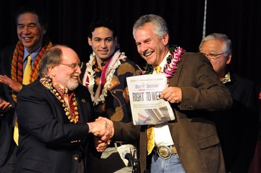 In this Nov. 13, 2013 file photo, Governor Neil Abercrombie, left, and former senator Avery Chumley hold up a copy of the Star Advertiser after Abercrombie signed the bill legalizing gay marriage in Hawaii in Honolulu.