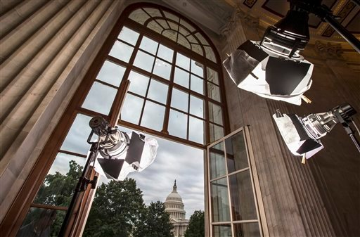 In this Sept. 9, 2013 file photo television news lights await the start of activity on Capitol Hill in Washington as both houses of Congress return to full legislative session.