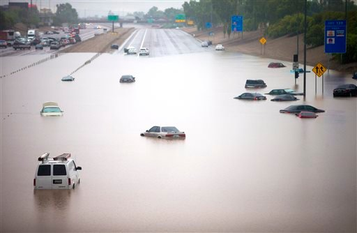 Cars are stuck in flood waters on I-10 east at 43rd Ave. after heavy storms pounded the Phoenix area early Monday, flooding major freeways, prompting several water rescues and setting an all-time single-day record for rainfall in the desert city.