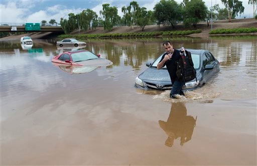 Jim Sampson retrieves items from his 2002 Toyota Corolla stuck in flood waters on I-10 east at 43rd Ave. after monsoon rains flooded the freeway in Phoenix, Monday, Sept. 8, 2014.