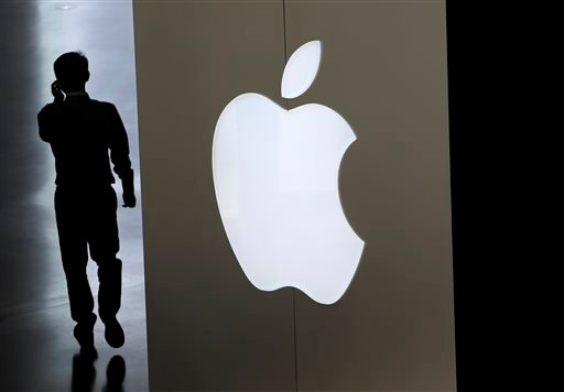 In this Sept. 5, 2014, file photo, a Chinese man talking on his phone walks into an Apple store in Beijing.
