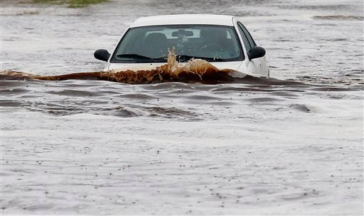 A driver tries to navigate a severely flooded street as heavy rains pour down Monday, Sept. 8, 2014, in Phoenix.