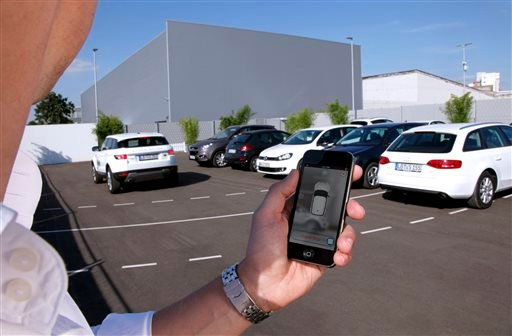In this undated photo supplied by Valeo, a person activates a self-parking vehicle via a smartphone application.