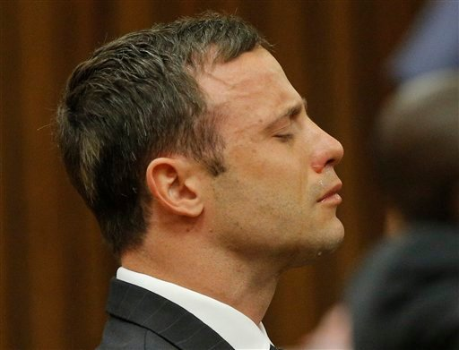Oscar Pistorius reacts in the dock in Pretoria, South Africa, Thursday Sept. 11, 2014 as Judge Thokozile Masipa reads notes as she delivers her verdict in Pistorius' murder trial.