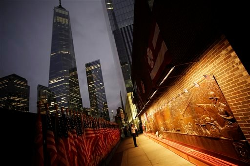 A firefighter looks at a memorial mural on the outside of firehouse Engine 10 Company 10 adjacent to the World Trade Center in New York, Thursday, Sept. 11, 2014. (AP)