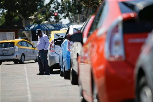 A cab driver waits near his car in line at a depot near the airport Wednesday, Sept. 10, 2014, in San Diego.