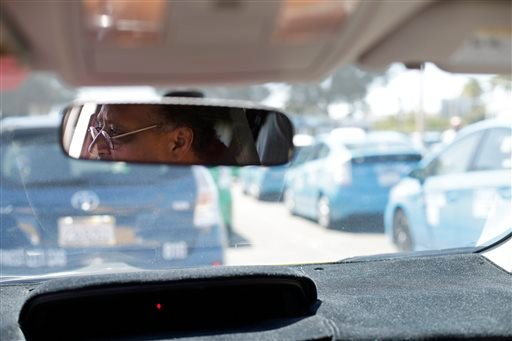 Cab driver Daniel Afeweki looks out from his Toyota Prius cab as he waits in line for his turn to pick up fares at the airport Wednesday, Sept. 10, 2014, in San Diego.