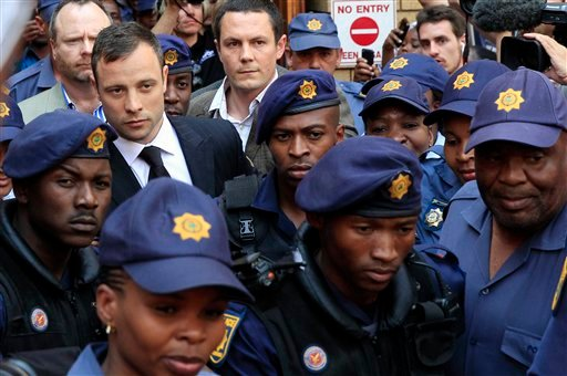 Escorted by police and security, Oscar Pistorius leaves the court in Pretoria, South Africa, Friday, Sept. 12, 2014.