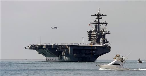 This Friday, Aug. 22, 2014 file photo the aircraft carrier USS Carl Vinson sails out of San Diego Harbor leaving for a nine month deployment in San Diego.