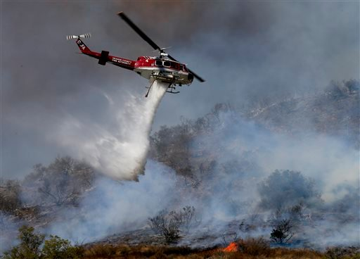 More than 280 firefighters are aided by water dropping helicopters and fixed-wing aircraft as they battle a 1,300-acre fire in Silverado Canyon, Calif., in Southern Orange County, Friday, Sept. 12, 2014. (AP Photo/Los Angeles Times, Mark Boster)