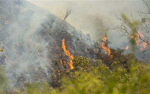 Flames burn a steep canyon in Silverado Canyon in Orange County, Calif. on Friday, Sept. 12, 2014. (AP Photo/Orange County Register, Sam Gangwer)