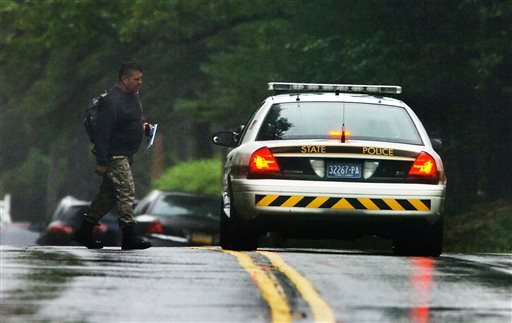 A Pennsylvania State Trooper walks by a state police vehicle on Route 402 on Saturday, Sept. 13, 2014, near the scene where a Pennsylvania State Trooper was killed and another trooper was injured during a shooting Friday night..