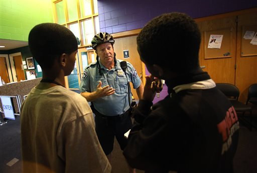 In a July 16, 2014 photo, Minneapolis police officer Mike Kirchen talks with Mohamed Salat, left, and Abdi Ali at the Brian Coyle Center in Minneapolis.