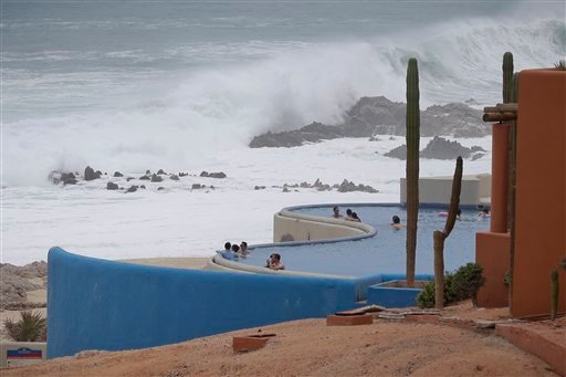 Tourists watch the ocean from inside a swimming pool at a resort in Los Cabos, Mexico, Sunday, Sept. 14, 2014.