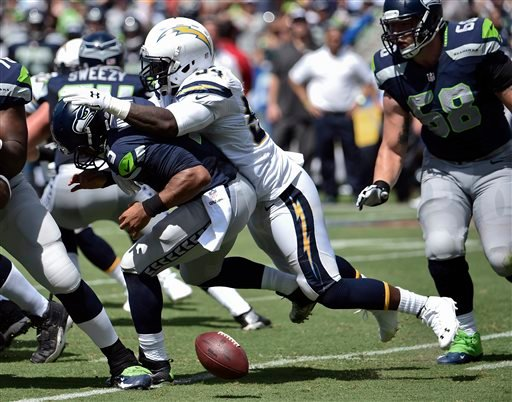 Seattle Seahawks quarterback Russell Wilson, left, fumbles as he is sacked by San Diego Chargers outside linebacker Melvin Ingram during the first half of an NFL football game on Sunday, Sept. 14, 2014, in San Diego. The Seahawks recovered the fumble.