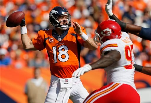 Denver Broncos quarterback Peyton Manning (18) throws under pressure from Kansas City Chiefs defensive end Allen Bailey during the first half of an NFL football game, Sunday, Sept. 14, 2014, in Denver. (AP Photo/Jack Dempsey)