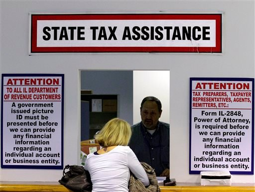 In this April 16, 2012 file photo, an Illinois Department of Revenue employee offers assistance to income tax payers at the Illinois Department of Revenue in Springfield, Ill.