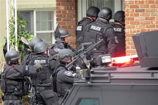 In this April 22, 2014, file phot, Nassau County police officers enter a home in Long Beach, N.Y., in search of an armed killer, based on a phone call that turned out to be a hoax.