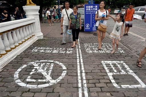 In this photo taken Saturday, Sept. 13, 2014, residents walk on a lane painted with instructions to separate those using their phones as they walk from others in southwest China's Chongqing Municipality.