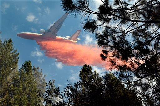 A jet air tanker drops its load of fire retardant on a fire burning in the area of Cedar Drive in Oakhurst, Calif., Sunday, Sept. 14, 2014, as two raging wildfires in the state forced hundreds of people to evacuate their homes.