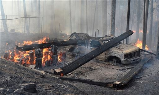 A burned truck and smoldering ruins is all that is left of a garage near a house that burned on Cedar Drive in Oakhurst, Calif., Sunday, Sept. 14, 2014, as two raging wildfires in the state forced hundreds of people to evacuate their homes.