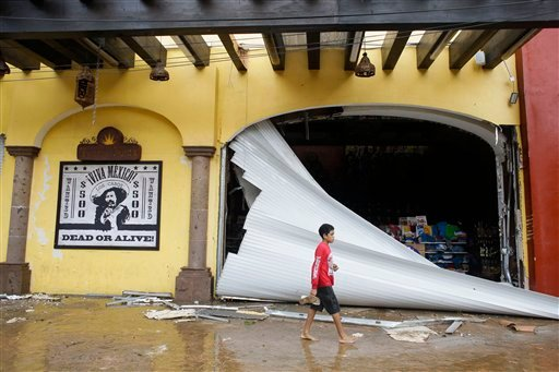 A kid walks by a souvenir store damaged by Hurricane Odile on San Lucas' main street, in Los Cabos, Mexico, Monday, Sept. 15, 2014.